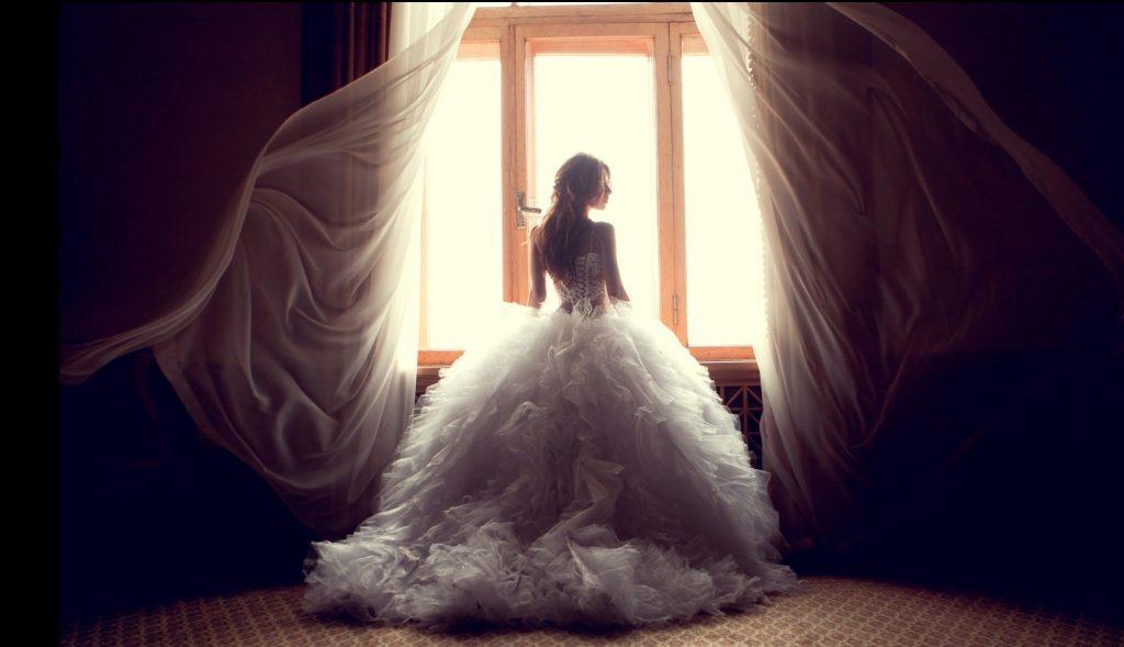 Brautkleid mit einem eng anliegenden, körperbetonenden Oberteil mit Schnür-Optik im Rücken und einem besonders üppigen Rock. (#1)