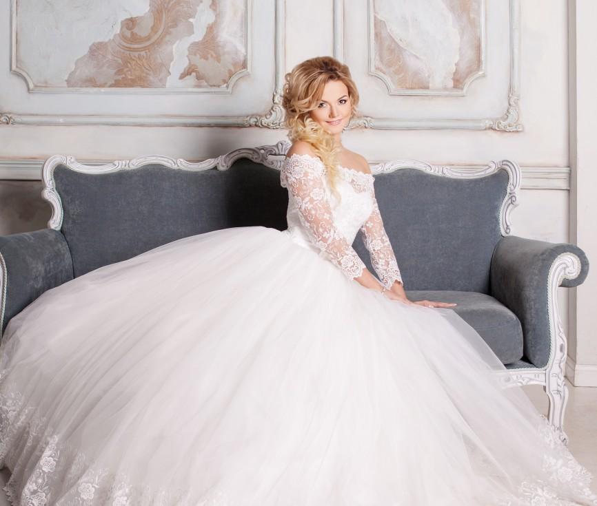 Das Hochzeitskleid aus Tüllund Spitze verwirrt mit einem zauberhaften Dekolleté. Ärmel in Dreiviertellänge aus durchbrochener Spitze. (#12)