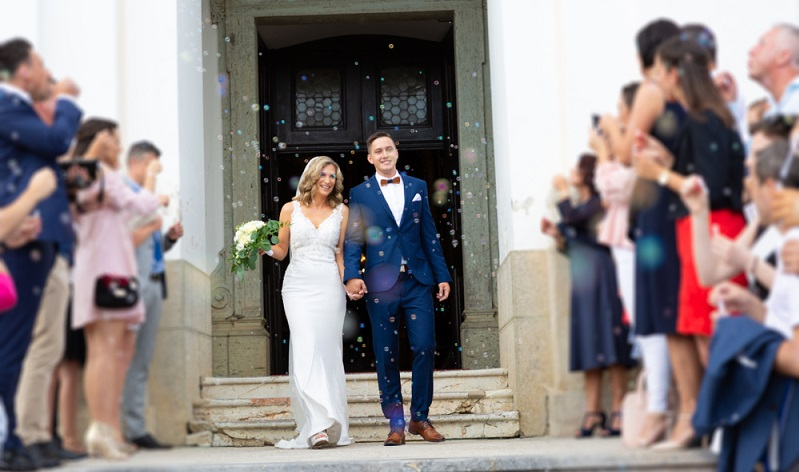 Die versammelte Hochzeitsgesellschaft stellt sich vor der Kirche auf und bildet aus Gegenständen, die symbolisch für das Brautpaar oder für ein Hobby des Paares stehen, ein Spalier.  ( Foto: Shutterstock-Matej Kastelic )